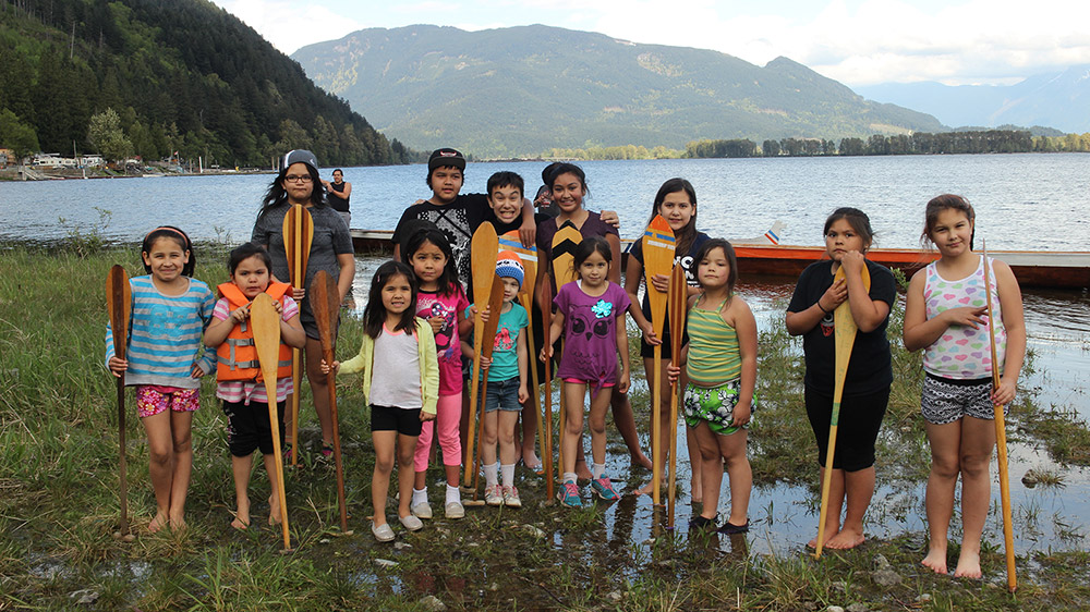 Fourteen young children stand near the shore of a river, smiling, and holding onto canoe paddles that are positioned in front of them vertically. A canoe is behind them. In the background is the river, and green mountains are in the distance.