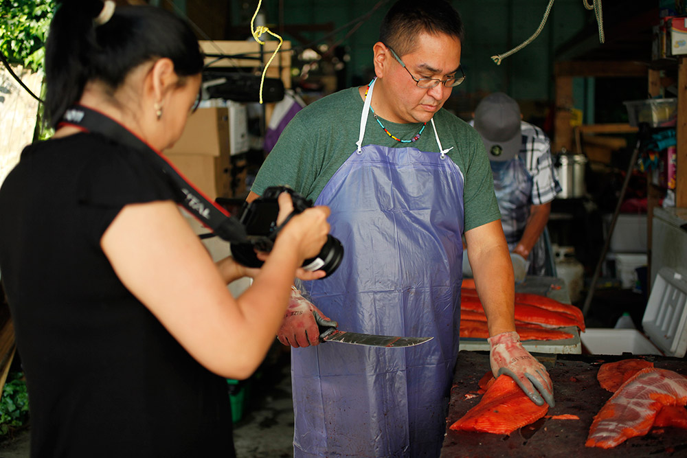 A woman is reviewing a photo on her camera in the foreground, and a man stands in front of her looking down at the salmon he is filleting. He is wearing a blue apron, and holds a knife in one hand.