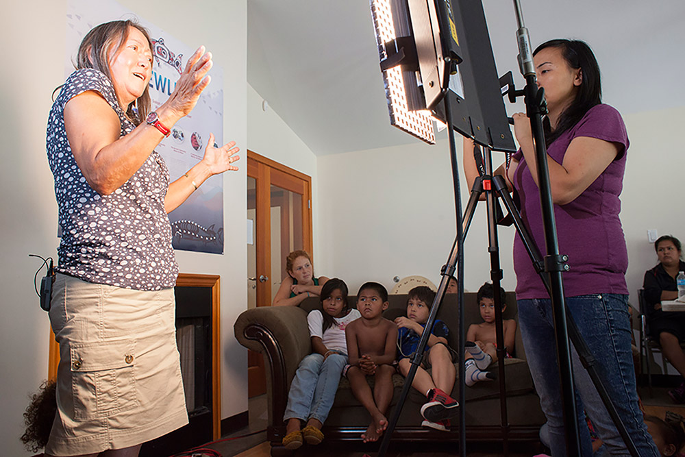 A woman is standing on the left side of the photo, sharing a story with children that are seated on a couch in the background. There is a woman on the right side that is filming the event.