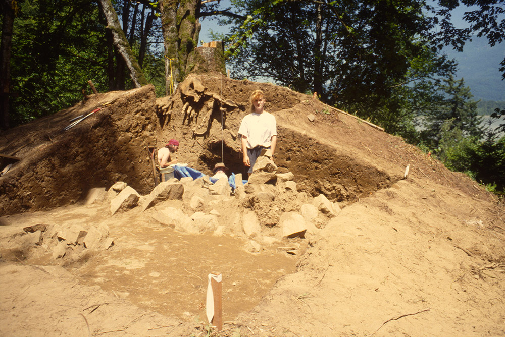 Several people are gathered alongside an excavated large mound of earth. The mound is 3 m tall and has been sectioned in half lengthwise. There are many large rocks towards the base of the mound.