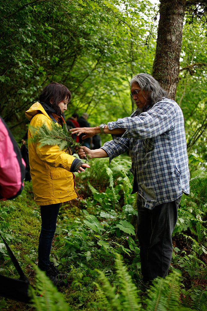 A man stands in a forested area, brushing a cedar branch along a woman's arms.