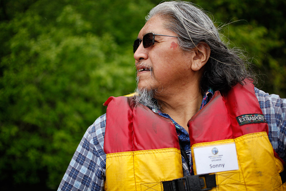 A man drives a small motorboat across the river. He wears a red and yellow lifejacket.