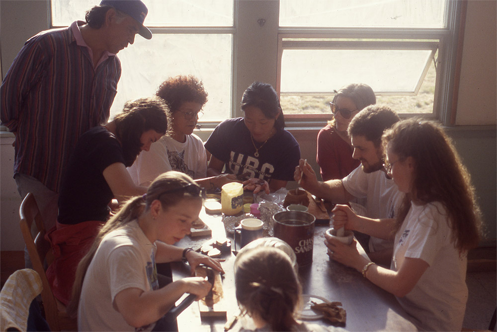 Many students are gathered at a rectangular table, using various tools and materials, including red ochre.