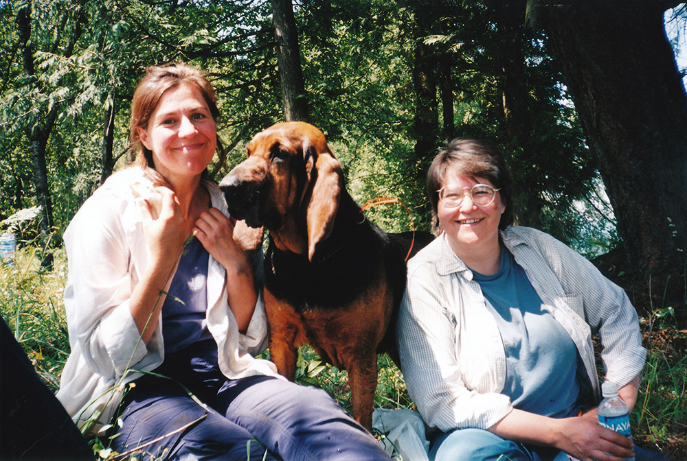 Two women sit on the grass, with a dog standing between them.