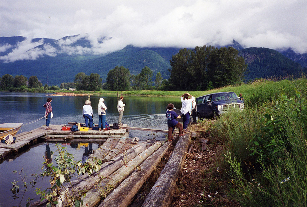 A group of field school students are standing on a wooden dock as they prepare to launch a boat into the river.