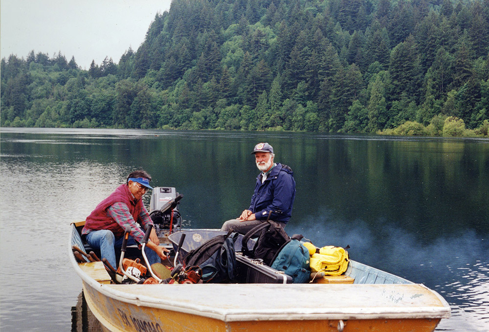 Two men sit in a small motorboat within the Harrison River.
