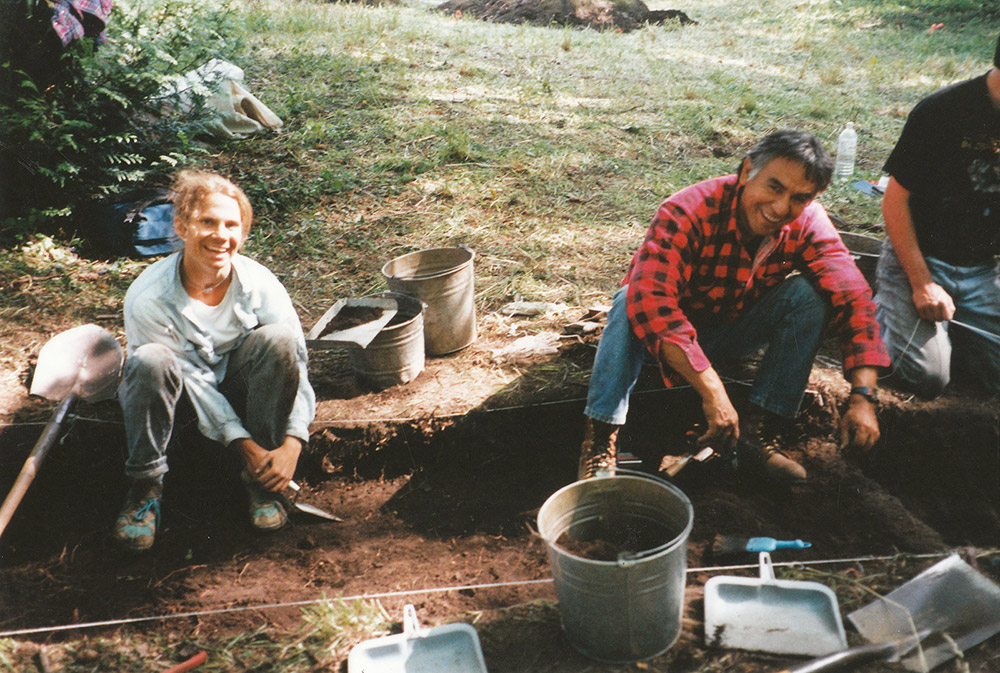 Two people sit within a sectioned archaeological area, using shovels to excavate the earth.