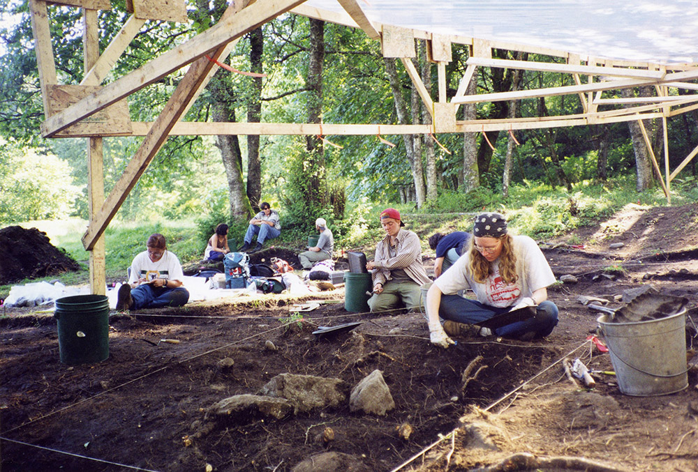 A group of archaeologists excavate the earth in sections; they are underneath a rain shelter.