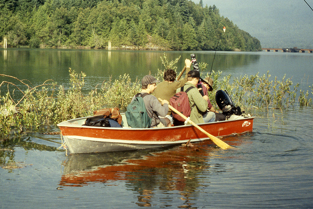 Four men are seated in a small motorboat in the river. The man closest to the bow is paddling the oars.
