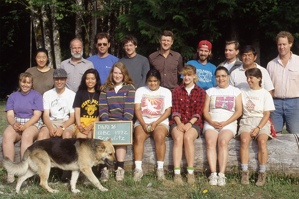 Two rows of people pose for a photograph. The front row is seated, and the back row is standing. The front-middle student holds a board with the class/year information. A dog walks in the foreground of the picture.