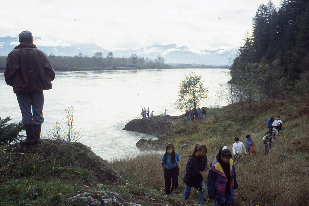 A group of people hike along the grassy shoreline; a man stands at a higher elevation looking back towards the river and mountains.