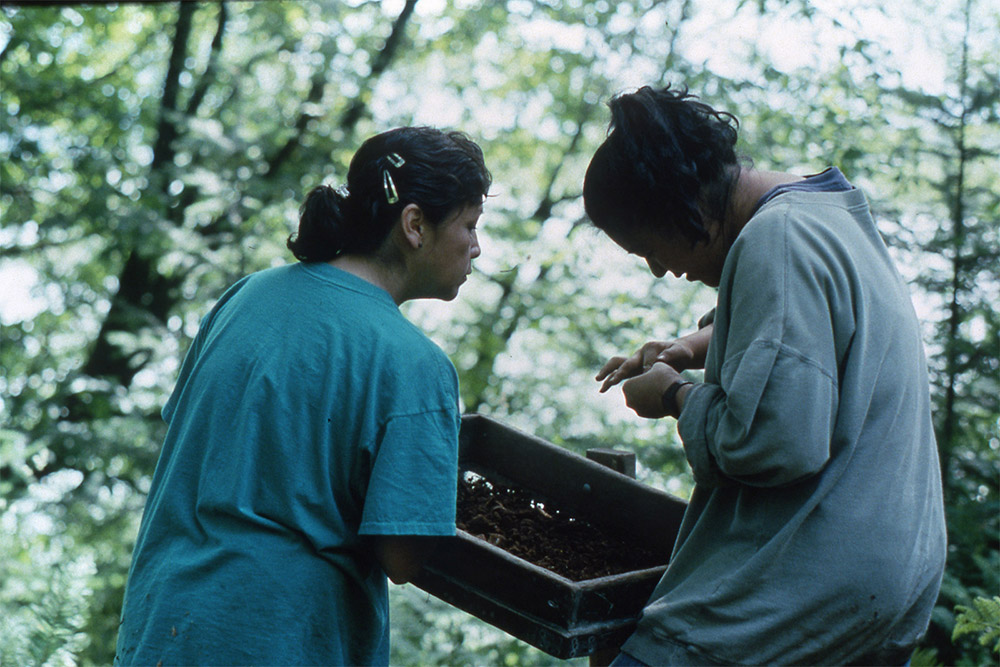 Two women hold up a wooden screen, sifting through dirt and examining the contents up close.