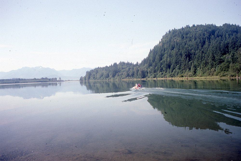 A group of people travel across the Harrison River by motorboat. The water is calm, and there are trees and mountains in the background.