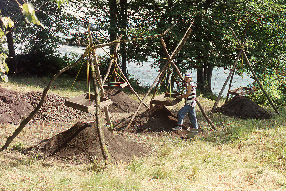 A woman stands beside a hanging wooden screen, sifting through dirt into a large mound below. There are many other hanging screens and dirt mounds set up around her.