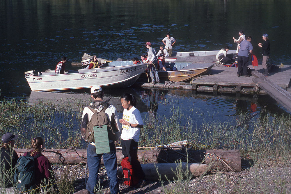 Students gather around a small wooden dock, loading supplies into boats.