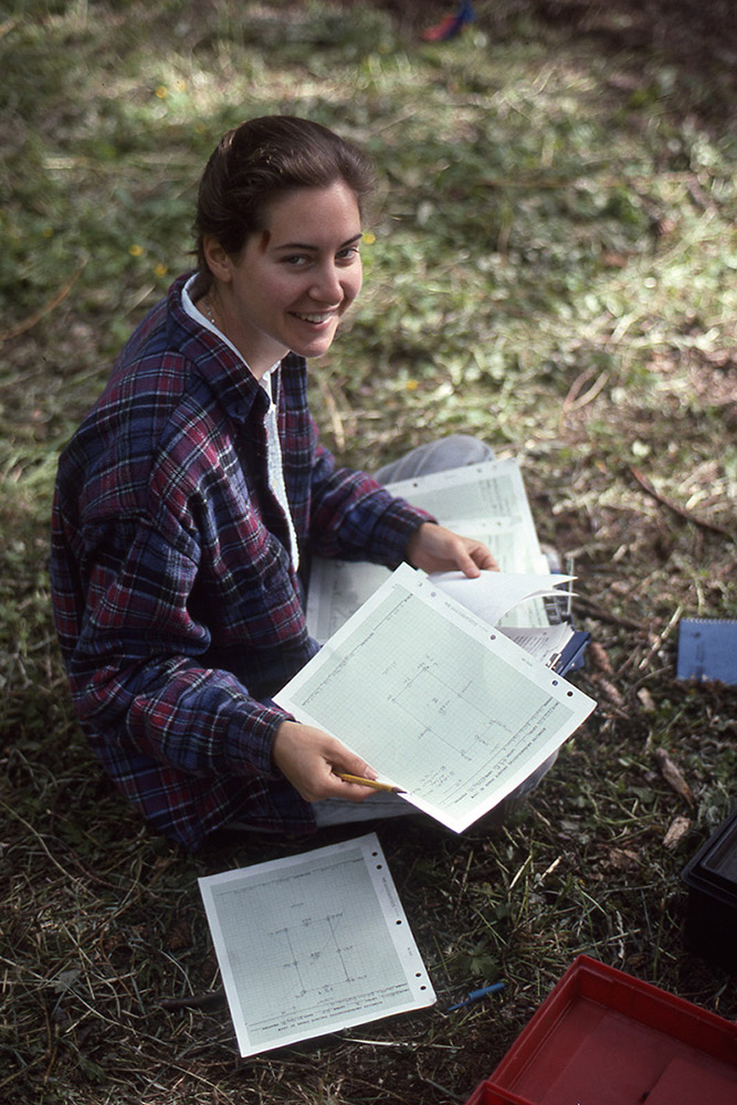 A woman sits on the grass and sorts through a pile of papers on her lap. She is smiling.