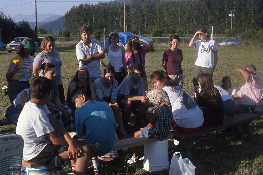 A group of students are gathered outside on a bench on a grass field, while a woman in the center explains the rules of a game.