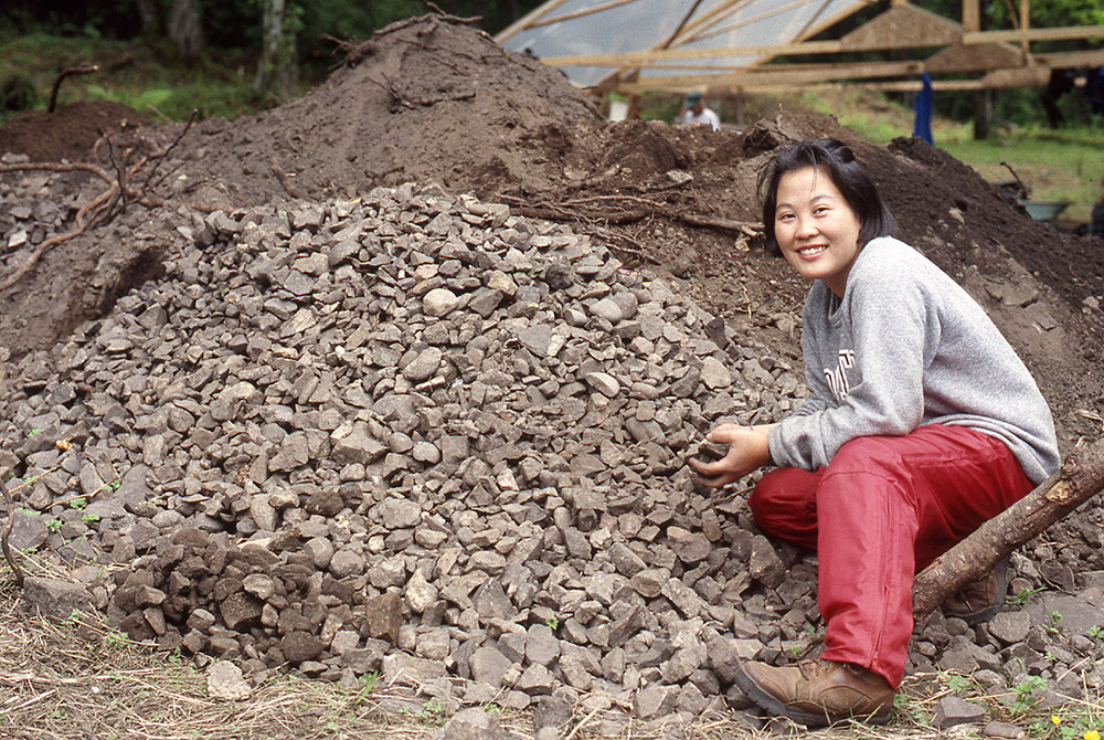 A woman sits beside a large pile of rocks, holding some in her hands.