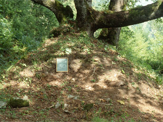 A large mound of earth is marked with a small sign.