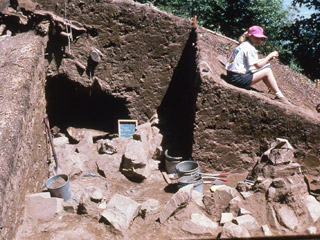 A woman sits beside an excavated section of earth. Inside this area is a large rock pile.