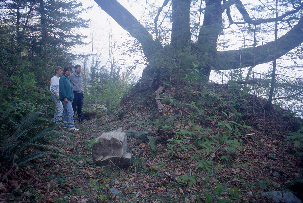 Three people stand beside an earthen mound with a large maple growing out of it.