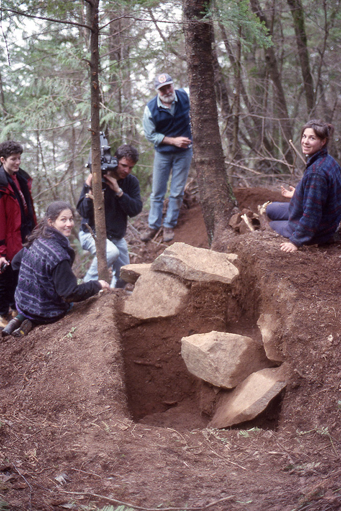 A group of archaeologists sit beside a section of earth that contains large boulders.