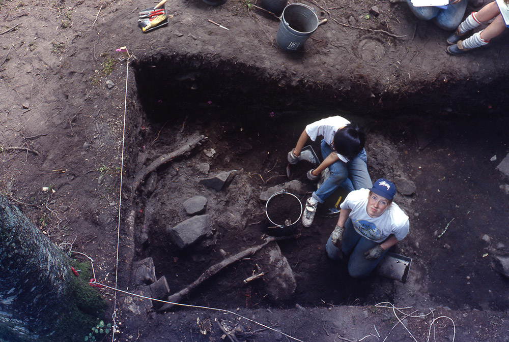 Two archaeologists sit in the section of earth they are excavating. The woman on the right is looking up at the camera.