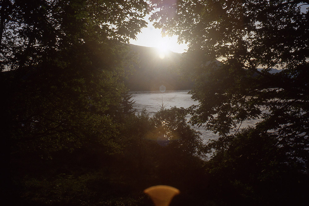 A view of the sun setting over a river with greenery framing the picture.