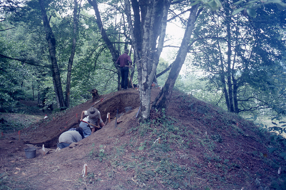 A group of archaeologists excavate a section of an earthen mound.