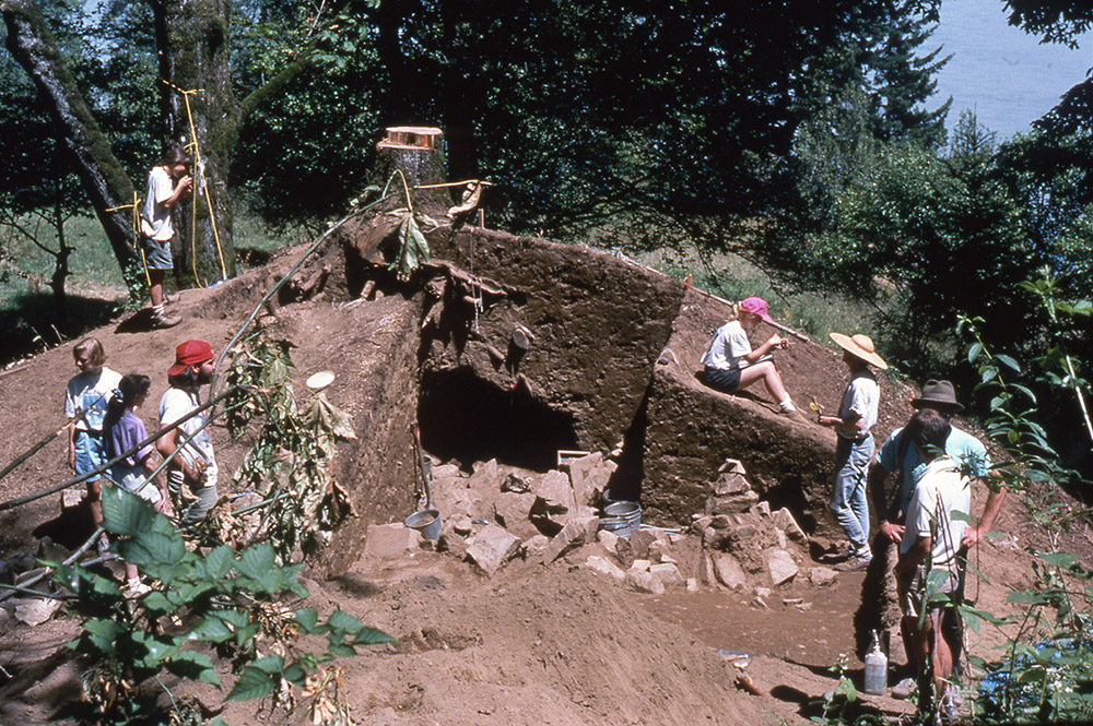 A group of archaeologists stand around the excavated sections of earth from a very large mound.