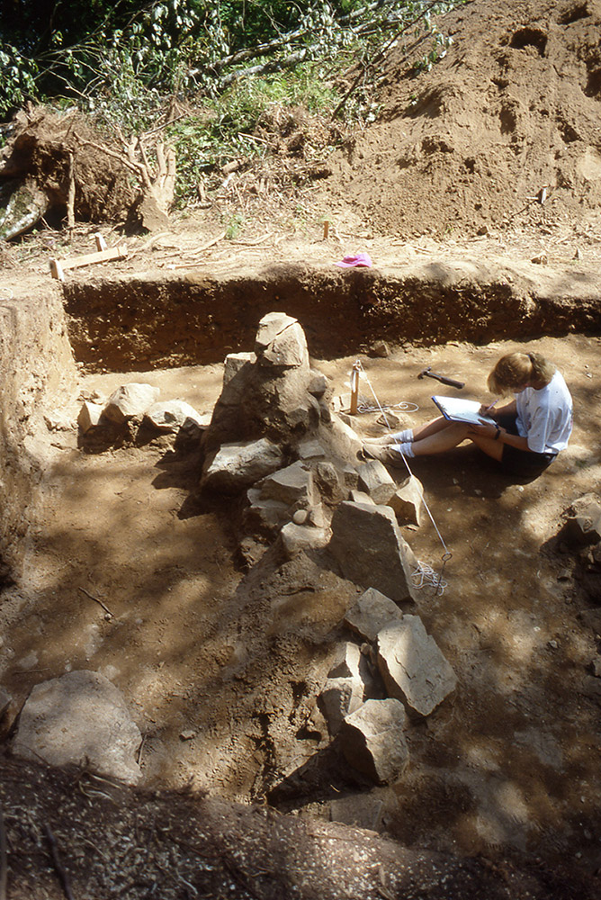 A woman takes field notes in front of a rock formation. She is seated beside an excavated mound.