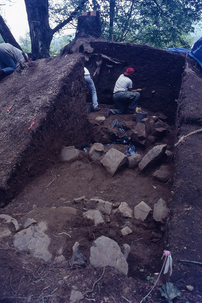 An archaeologist excavates part of an earthen mound.