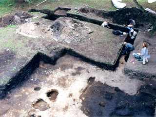 An aerial view of a group of archaeologists working in an archaeological area.