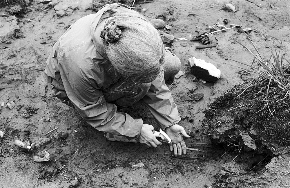 A black and white photograph of a woman in an archaeological area. She is spraying ancient basketry remains with water to expose them.