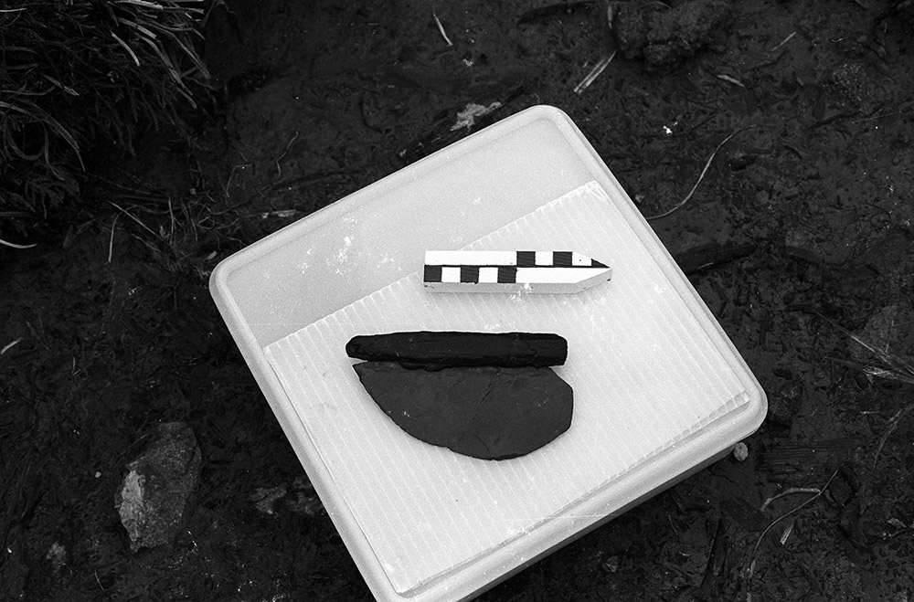 A black and white photograph shows an ancient stone knife with a wooden handle in the archaeological area it was found.