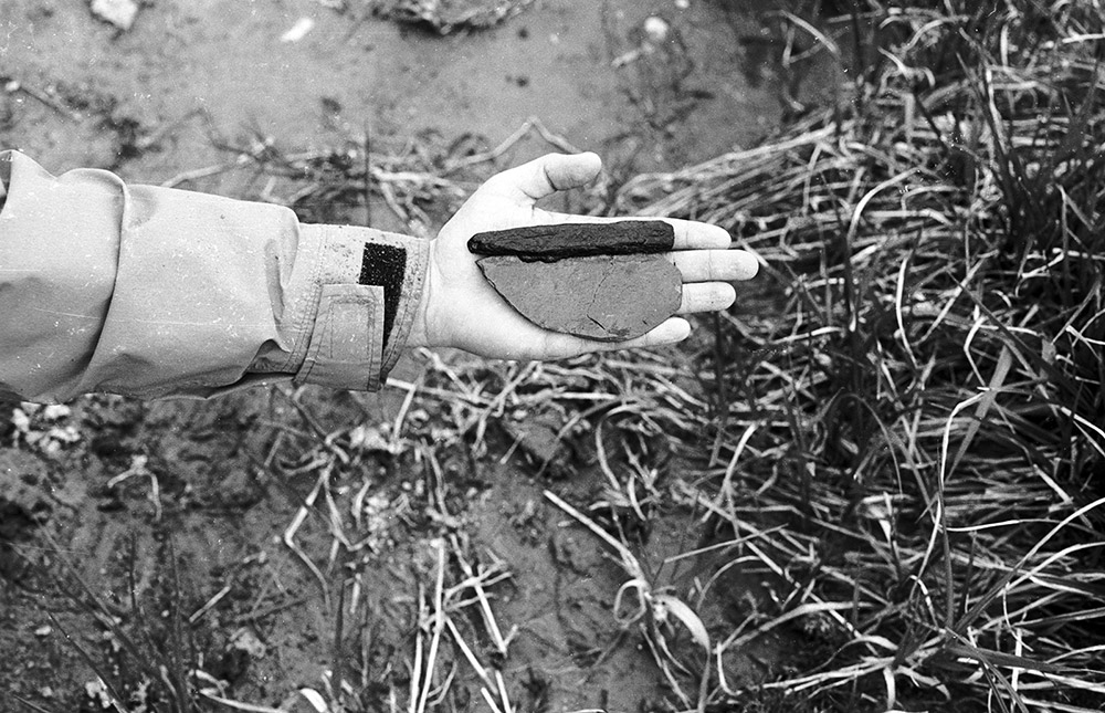 A black and white photograph shows someone holding an ancient stone knife with a wooden handle in the palm of their hand.