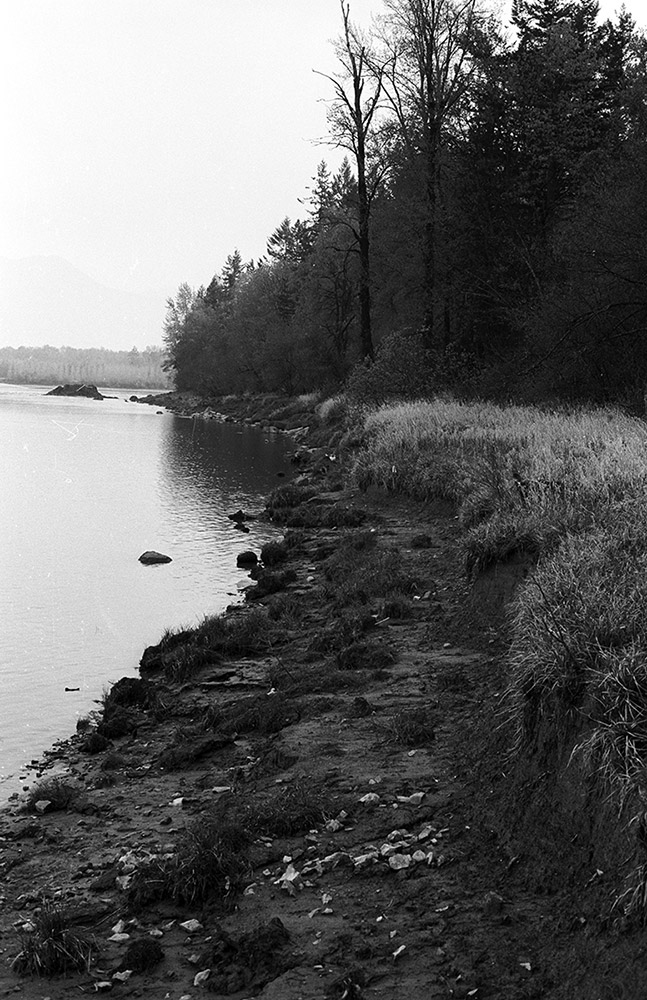 A black and white photograph shows the shoreline when the river's waters are low.