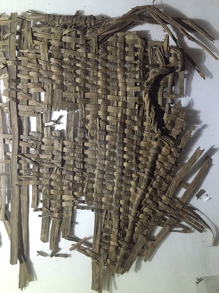 A fragmented basket woven from bark strips. Parts of the rim, body, and handle of the basket are still preserved.