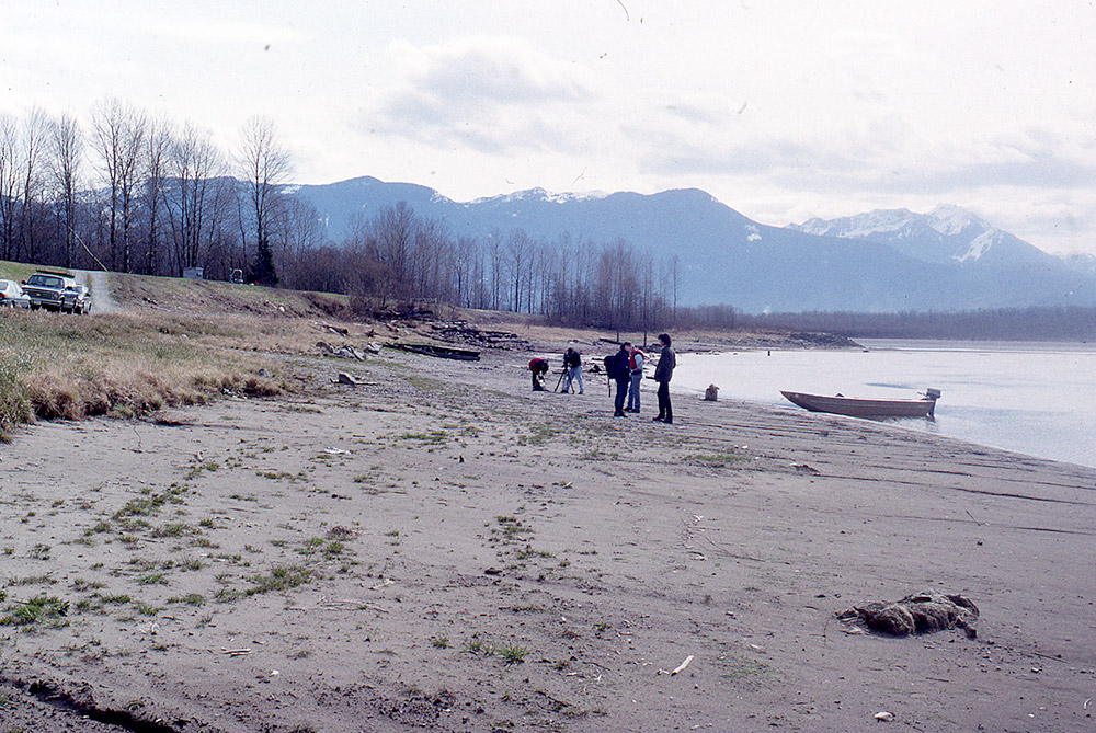 A group of people stand on the shoreline; a small motorboat has been pulled up onto the beach.