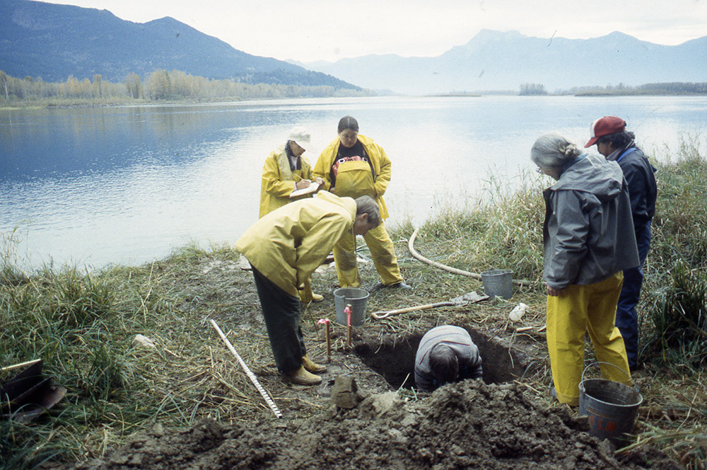 A group of people watch as one person excavates a section of earth on the riverbank.