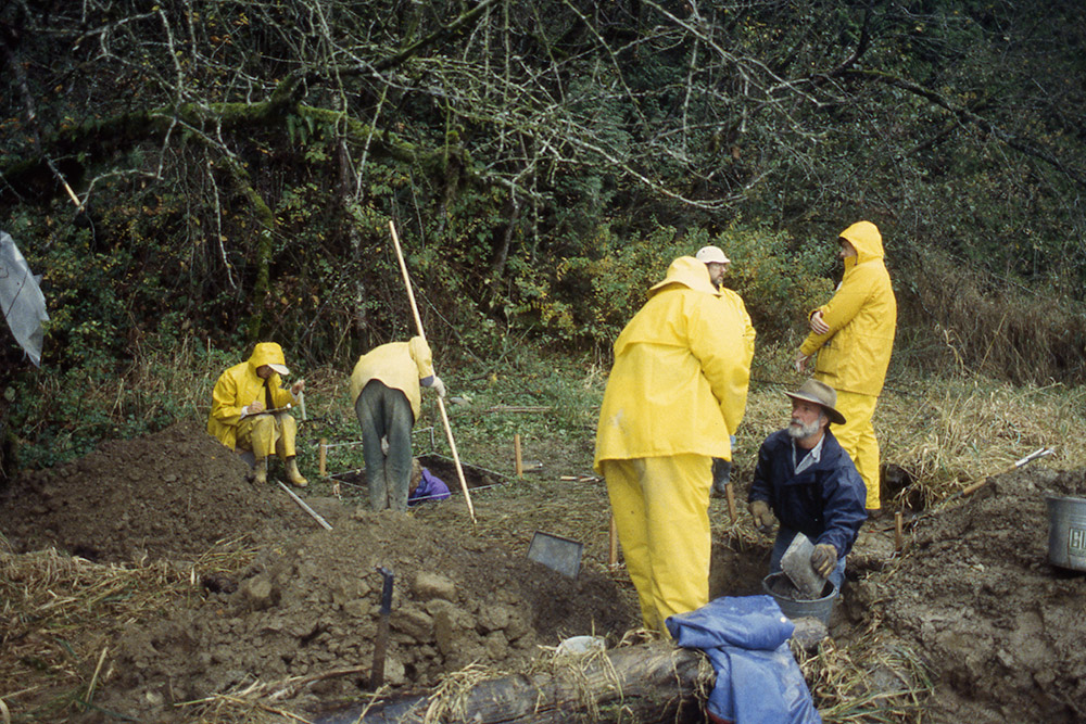 A group of people wearing raingear work in an archaeological area.