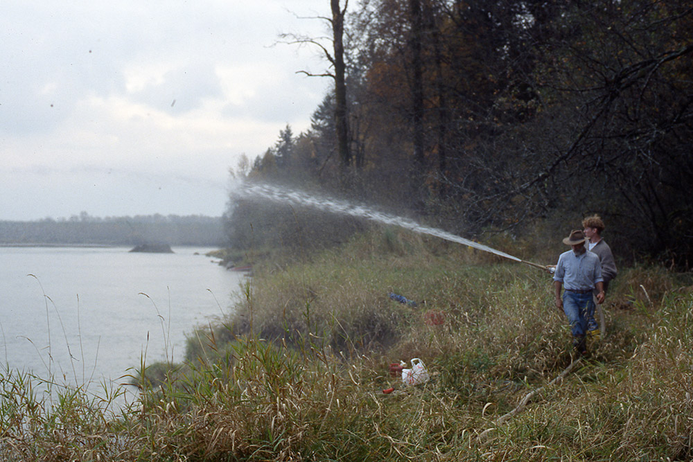 Two people stand on the riverbank. One holds a hose that is spraying a large stream of water into the air towards the river.