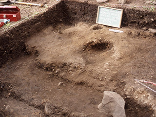 An open archaeological excavation with a hole exposed in the dirt.
