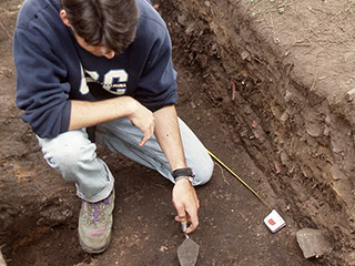 A person examining an archaeological excavation site with a trowel in hand.