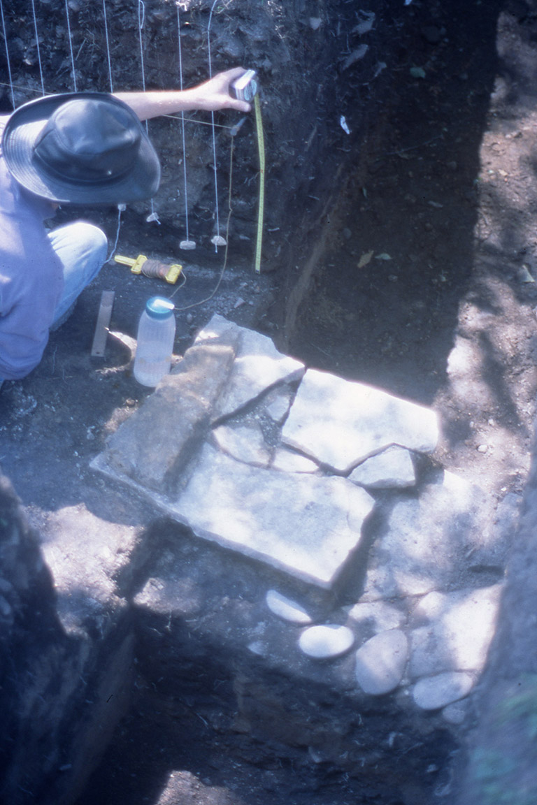 A person kneeling next to flat-fitted square stones, taking measurements.