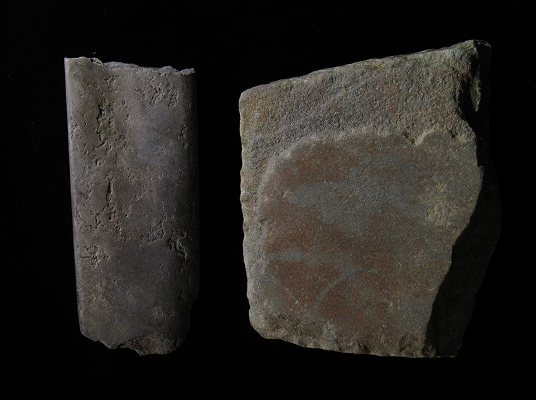 Two pieces of grey stone shaped into flat square pieces.
