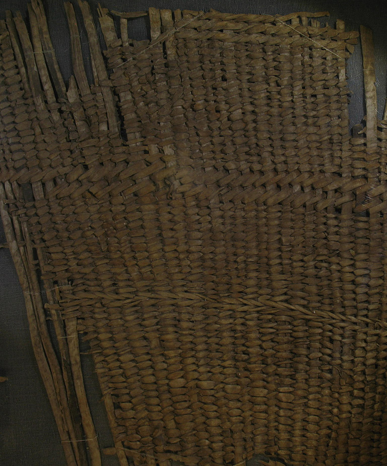 A fragment of woven basketry. The weaving material is brownish red.