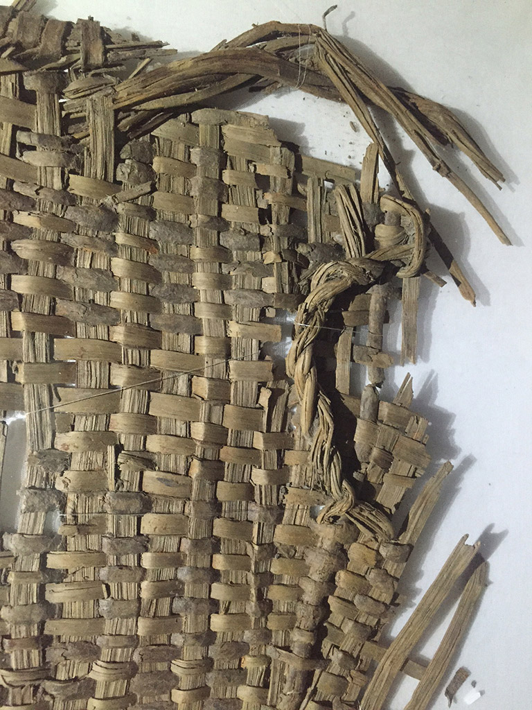 A fragment of  basketry with a woven handle on upper right. The color is light greyish brown.