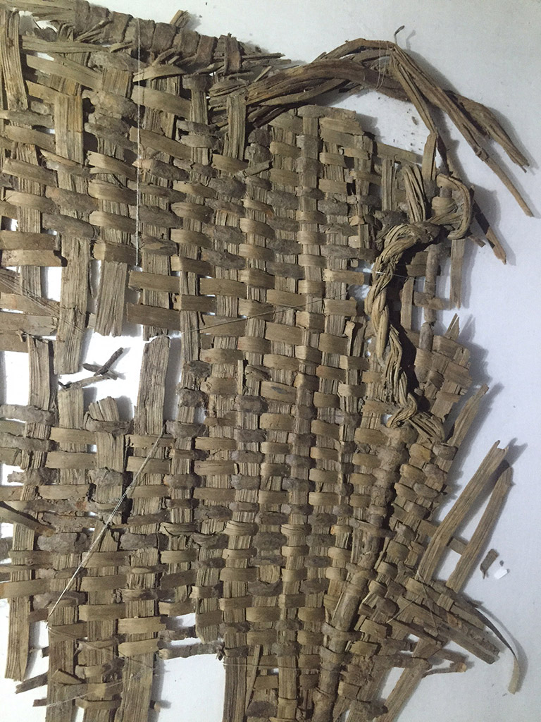 A fragment of woven basketry. The weaving material is light greyish brown.