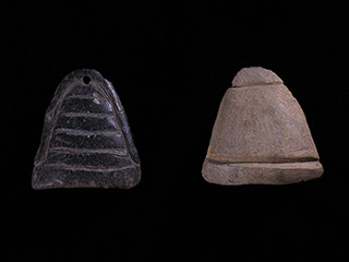 Two small small stone pieces carved into a triangular shape.The black one has an engraved outline and five horizontal lines, and is pierced. The light one has lines etched at the top and bottom.